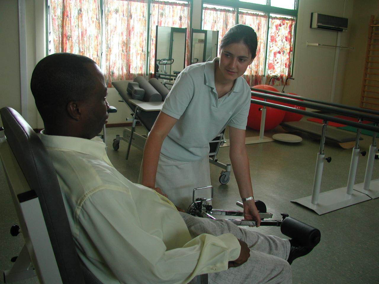An intern from Projects Abroad is pictured helping a man stretch as part of her physiotherapy internship in Ghana.